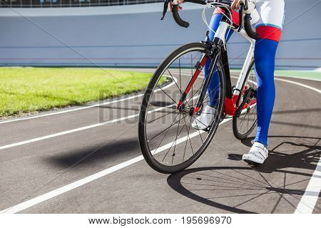 Young professional cyclist on a velodrome, closeup