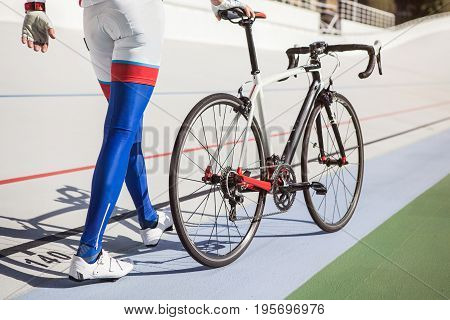 Young professional cyclist on a cycle track have a rest