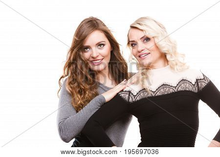 Generation relationship and outfit concept. Portrait adult daughter with mother. Two attractive elegant women wearing dresses long curly hairs blonde mom and brown haired girl