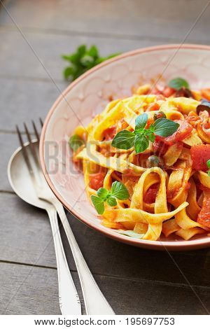 Tagliatelle pasta with tomato sauce and olives