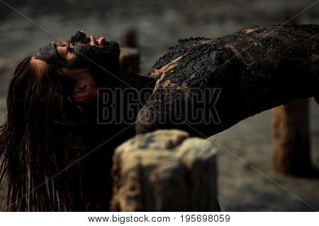 Young woman smeared with therapeutic mud and lies on wooden column. Mud forms crust on her body. Spa.