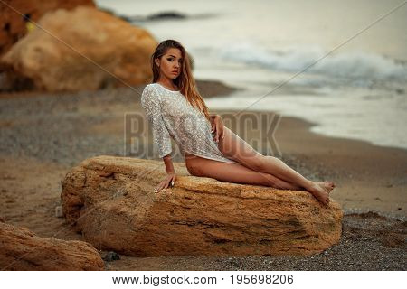Young woman in white lacy dress lies on rock on pebble beach by the sea. In background there are surf.