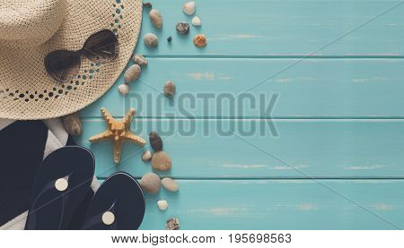 Sea vacation background on blue wood, top view with copy space. Beach accessories, flip flops and seashells