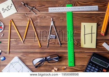 Text math composed of pencils, rulers, circular, sharpener and sticker with the letter. Math concept.
