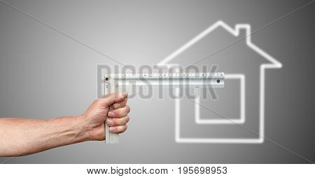 Hand with ruler and house on a grey background
