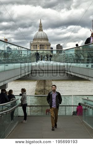 LONDON, UK - JUNE 5 , 2017:  Tourists walking across the Milenium bridge to St. Paul Cathedral by a cloudy day in London