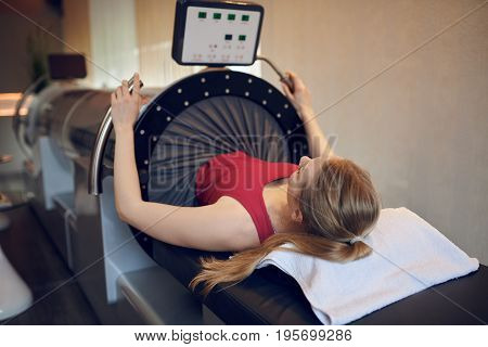 Attractive fit young woman doing vacuum therapy for prevention and regeneration smiling at camera