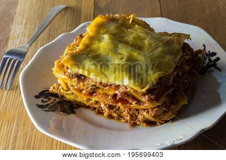 Traditional lasagna made with minced beef bolognese sauce and bechamel sauce topped with mozarella close up romantic rustic dinner