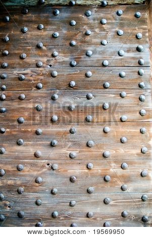 Traditional Roman reinforced wooden door closeup, from entrance to old fortified village