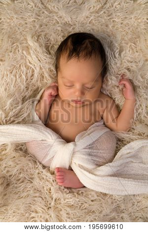 Mixed race African baby of 7 days old sleeping on a cream blanket
