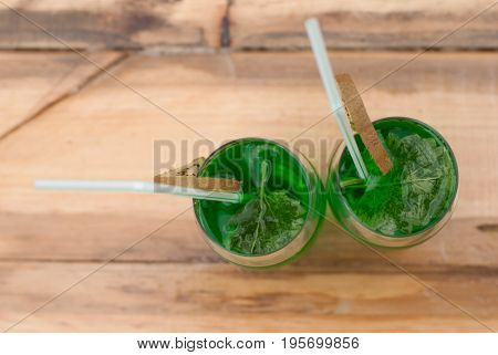 a glass of cold fresh green drink on the wooden bar, top view, background for St. Patrick's day. cocktail with kiwi