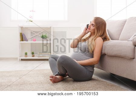 Smiling pregnant woman talking on her smartphone. Happy expectant blonde have pleasant talk on phone and touching her belly, sitting on floor, copy space