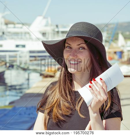 Travel deals concept. Happy smiling woman with tickets for the cruise at the port resort city. journey through water. Rest time at sea.