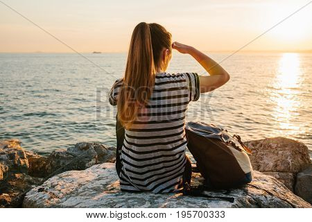 A young tourist girl with a backpack sits on the rocks next to the sea at sunset and looks into the distance. Relaxation, travel, vacation.