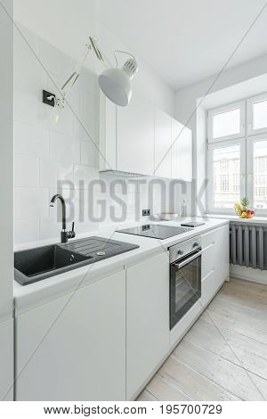 White kitchen with sink worktop simple cupboards and window