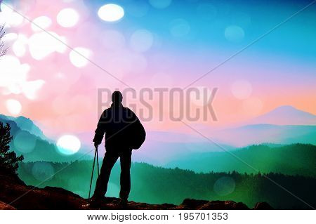Film Grain.  Silhouette Of Tourist With Poles In Hand. Hiker With Sporty Backpack Stand On Rock