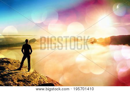 Film Grain. Man Stands On Rock Abve Valley Within Daybreak And Watch To Hot Sun. Beautiful Moment Th