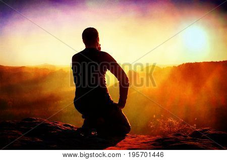 Film Grain. Sportsmann Hiker In Black Sportswear Sit On Mountain Top And Take A Rest With Watching D