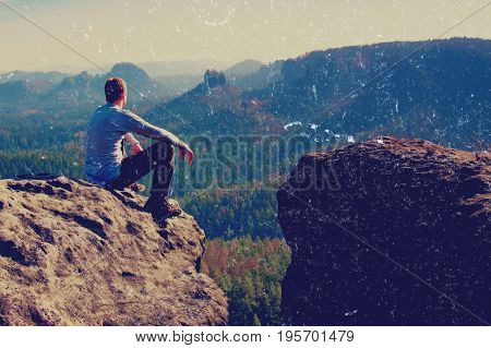 Film Grain. Young Man In Black Sportswear Is Sitting On Cliff's Edge And Looking To Misty Valley Bel