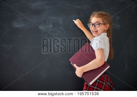 Back to school! Happy cute industrious child indoors. Kid is learning in class on background of blackboard.