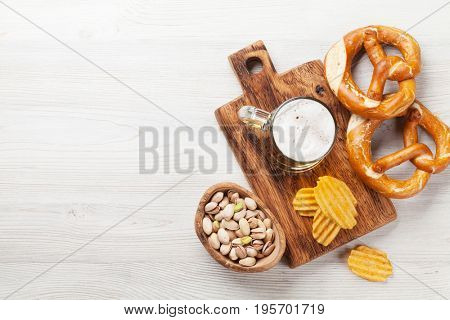 Lager beer and snacks on wooden table. Nuts, chips, pretzel. Top view with copy space