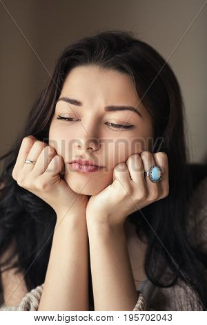 Tired woman portrait with empty and bored eyes. Mixed race asian caucasian model indoors