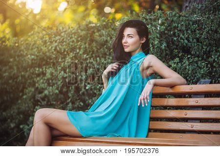 Charming young woman with long hair in dress sitting on a bench in a city park. Attractive young multi-racial Asian Caucasian gorgeous girl model resting outdoors