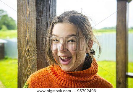 Girl teenager in an orange sweater