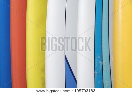 Row in vertical of several colorful surfboards