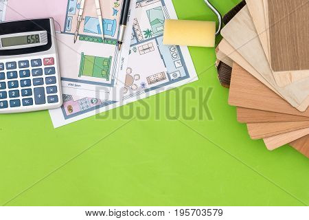 House Project With Wooden Sampler, Pen, Calculator On Green Background