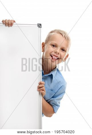 Funny schoolboy looking out whiteboard and showing tongue