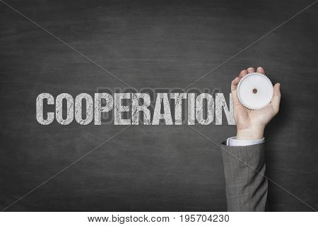 Cooperation text with businessman hand holding cogwheel