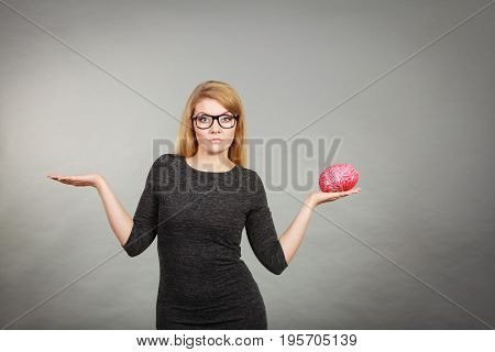 Woman In Eyeglasses Being Confused Holding Brain