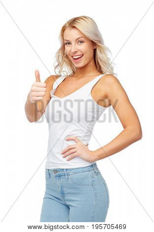 gesture, expressions and people concept - happy smiling young woman in white top and jeans showing thumbs up