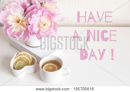 Bouquet of peonies, tea with lemon, photo in gentle colors. Good morning. Have a nice day! Inscription - have a good day