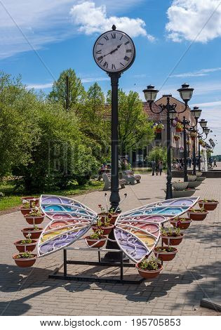 Sortavala, Republic of Karelia, Russia - June 12, 2017: Public garden with a city clock and a decorative flower bed. Decorative flower bed is made in the form of a butterfly with multi-colored wings.