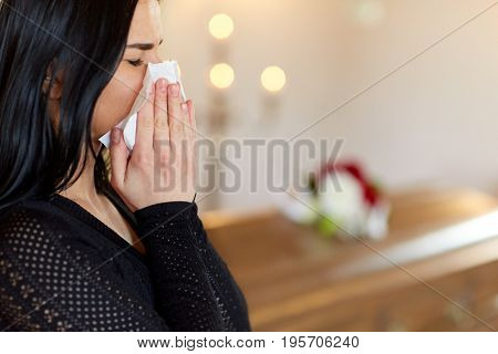 people and mourning concept - close up of crying woman with coffin at funeral in church