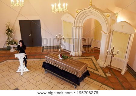 people and mourning concept - crying woman near coffin at funeral in christian orthodox church