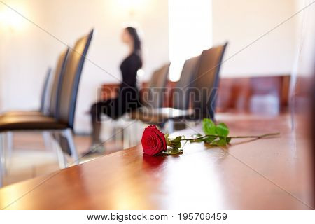 people and mourning concept - red roses and woman crying at funeral in church