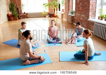 fitness, sport and healthy lifestyle concept - group of people with water bottles and towels in yoga class resting on mats at studio
