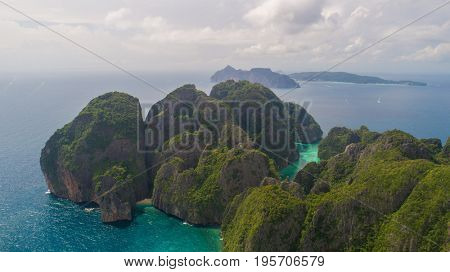 Aerial drone view of tropical turquoise water Loh Samah Bay and Maya Bay surrounded by limestone cliffs, Phi Phi islands, Thailand