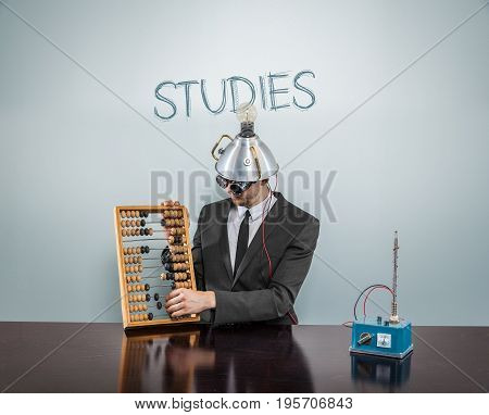 Studies text on blackboard with businessman and abacus