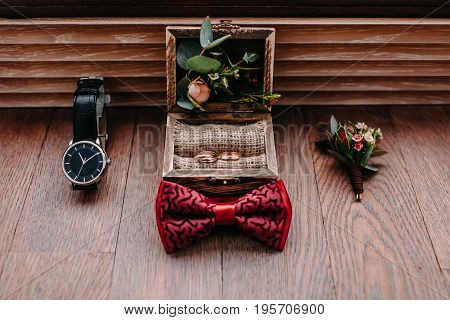 Stylish groom's accessories on a wooden background. Bow tie, boutonniere, and golden rings. Preparation for wedding concept.
