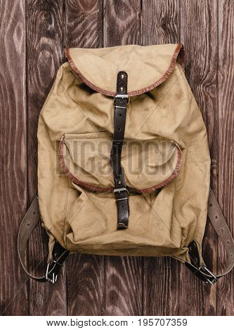 Old military backpack on wooden background top view.