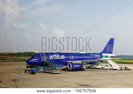 Grenada June 26 2017: JetBlue airplane is being prepared by ariport crew for its flight to NYC.