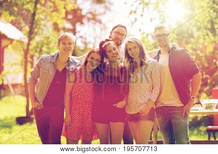 leisure, holidays, reunion, people and friendship concept - happy teenage friends hugging at summer garden party