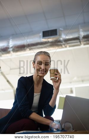 Smiling businesswoman holding disposable cup while sitting with laptop at table