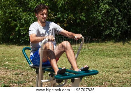 young man outdor exercise on rowing machine summer day