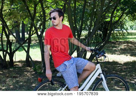 casual young man with sunglasses on bike in wood  making pause