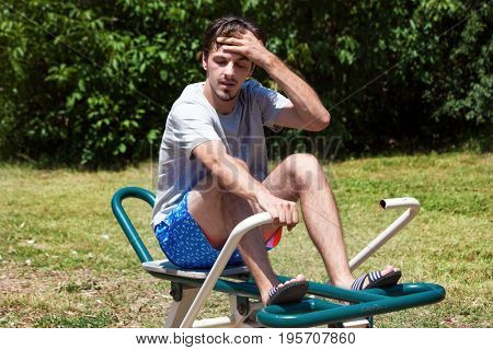 tired young man after exercise on rowing machine in park outdoor summer hot day